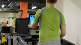 Hombre joven fuerte en la rueda de ardilla en gimnasio almacen de video