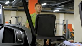 Hombre joven fuerte en la rueda de ardilla en gimnasio metrajes