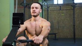 Hombre joven fuerte que entrena detrás en el simulador del deporte en el gimnasio almacen de metraje de vídeo