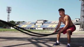 Hombre joven fuerte que hace ejercicios con una cuerda de la batalla al aire libre en día soleado almacen de video