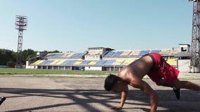 Hombre joven fuerte que hace ejercicios con una cuerda de la batalla al aire libre en día soleado metrajes