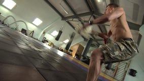 Hombre joven fuerte que hace ejercicios con una cuerda de la batalla de la velocidad almacen de metraje de vídeo