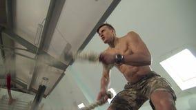 Hombre joven fuerte que hace ejercicios con una cuerda de la batalla de la velocidad almacen de video