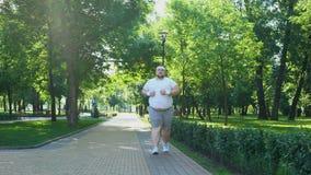Hombre joven gordo que activa en el parque, concepto de la obesidad, luchando con inseguridad metrajes