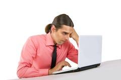 Hombre joven gruñón enojado con el ordenador portátil que mira el monitor sobre w Fotografía de archivo