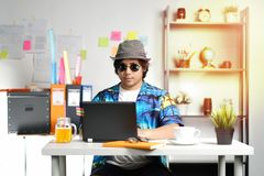 Hombre joven hawaiano que trabaja con el ordenador portátil el la estación de vacaciones de verano Fotografía de archivo libre de regalías