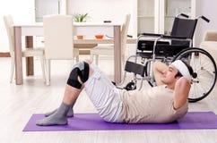 Hombre joven herido que hace ejercicios en casa foto de archivo libre de regalías
