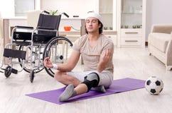Hombre joven herido que hace ejercicios en casa imagenes de archivo