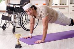 Hombre joven herido que hace ejercicios en casa fotos de archivo libres de regalías