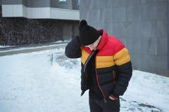 Hombre joven hermoso al aire libre en la chaqueta colorida del invierno que mira lejos el fondo urbano gris frío Fotografía de archivo