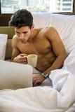Hombre joven hermoso atractivo en cama con la taza del café o de té Fotografía de archivo