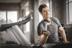 Hombre joven hermoso caucásico apto y músculo grande en ropa de deportes Hombre joven que lleva a cabo pesa de gimnasia durante u imagenes de archivo