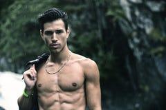 Hombre joven hermoso cerca de la cascada de la montaña con la camisa en hombro Imagen de archivo libre de regalías