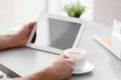 Hombre joven hermoso con café de consumición de la tableta imagen de archivo
