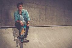 Hombre joven hermoso con el monopatín al aire libre Foto de archivo libre de regalías