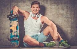 Hombre joven hermoso con el monopatín al aire libre Fotografía de archivo libre de regalías