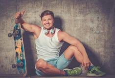 Hombre joven hermoso con el monopatín al aire libre Fotografía de archivo