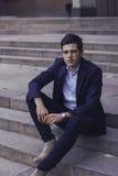 Hombre joven hermoso con el pelo diseñado El hombre se está sentando en los pasos Foto de archivo libre de regalías