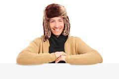 Hombre joven hermoso con el sombrero de piel que presenta behing un panel Imagen de archivo