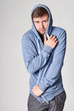 Hombre joven hermoso con la barba ligera en sudadera con capucha azul, en el CCB gris Imagen de archivo libre de regalías