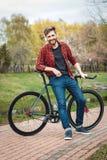 Hombre joven hermoso con la bicicleta Foto de archivo libre de regalías