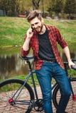 Hombre joven hermoso con la bicicleta Imagen de archivo libre de regalías