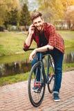 Hombre joven hermoso con la bicicleta Imagenes de archivo