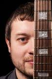 Hombre joven hermoso con la guitarra Cierre para arriba Foto de archivo libre de regalías