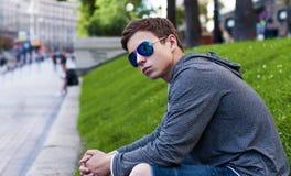 Hombre joven hermoso con los vidrios que se sientan en la hierba Fotografía de archivo libre de regalías
