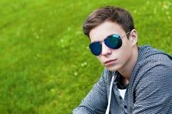 Hombre joven hermoso con los vidrios que se sientan en la hierba Imágenes de archivo libres de regalías