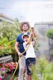 Hombre joven hermoso con su hijo que juega con la manguera en el invernadero Imagenes de archivo