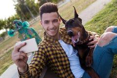 Hombre joven hermoso con su perro usando el teléfono móvil en el parque Fotos de archivo libres de regalías