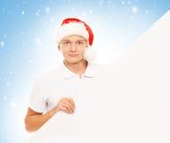Hombre joven hermoso con una cartelera en blanco en un fondo de la Navidad Imagenes de archivo
