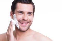 Hombre joven hermoso con una espuma que afeita Imagenes de archivo