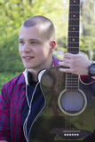 Hombre joven hermoso con una guitarra en el parque Fotografía de archivo libre de regalías