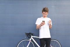 Hombre joven hermoso con una taza de café que se coloca en el fondo de una pared cerca de una bicicleta imagen de archivo