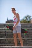 Hombre joven hermoso de moda con un monopatín en fondo de las escaleras de la calle Forma de vida y concepto activos de la juvent fotografía de archivo libre de regalías