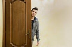Hombre joven hermoso detrás de la puerta abierta, saliendo Fotografía de archivo