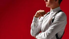 Hombre joven hermoso elegante pensativo en una camisa blanca y una correa de espada, en un fondo rojo imagenes de archivo