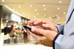 Hombre joven hermoso en alameda de compras usando el teléfono móvil Foto de archivo libre de regalías