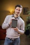 Hombre joven hermoso en casa con la tableta en sus manos Imagenes de archivo