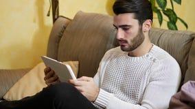 Hombre joven hermoso en casa, usando la tableta