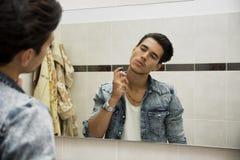 Hombre joven hermoso en cuarto de baño, cologne de rociadura o perfume Fotos de archivo
