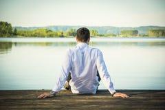 Hombre joven hermoso en el lago en un soleado, pacífico Imagen de archivo