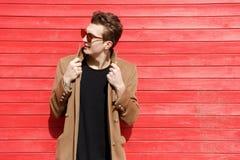 Hombre joven hermoso en gafas de sol y la situación de la chaqueta foto de archivo