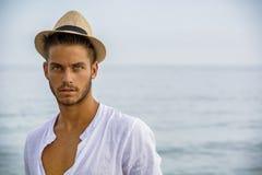 Hombre joven hermoso en la playa en día de verano Imagen de archivo libre de regalías