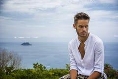 Hombre joven hermoso en la playa en día de verano Imagenes de archivo