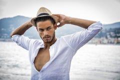 Hombre joven hermoso en la playa en día de verano Imagen de archivo