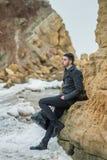 Hombre joven hermoso en la playa en las rocas Imagen de archivo libre de regalías