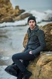 Hombre joven hermoso en la playa en las rocas Imágenes de archivo libres de regalías